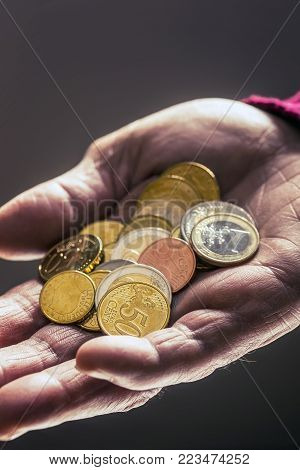 Pensioner Man Holding In Hands Euro Coins. Theme Of Low Pensions.