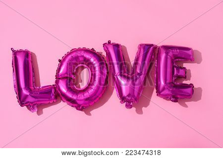 some fuchsia letter-shaped balloons forming the word love against a pink background