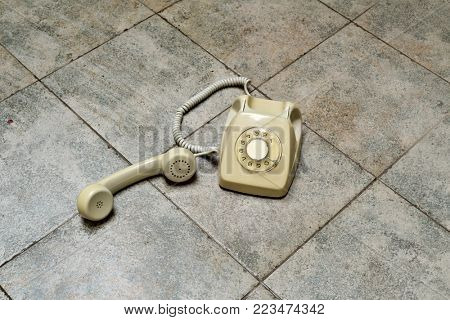 a retro rotary telephone with its handset off the hook on a tiled floor