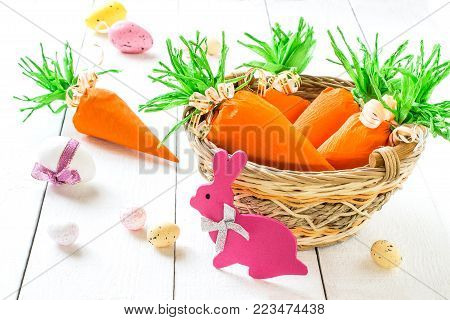 Handmade packages in form of carrots for Easter bunny. Sweet gift to children. Carrots from crepe paper with sweets in basket. Idea of decoration for children's party. Easter decorative eggs and bunny