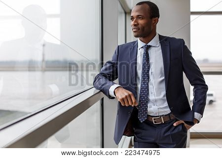 Feeling relaxed. Elegant experienced adult african businessman in suit is standing and looking through the window thoughtfully while holding hand in pocket of his pants. Copy space in the left side