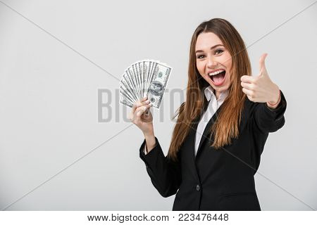 Cheerful beautiful brunette lady in official wear showing thumb up and dollars while looking camera isolated