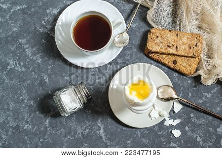 Soft-boiled egg in ceramic egg-cup, cup of coffee and cereal crispbread. Boiled fresh broken egg with liquid orange yolk, pieces of shell and spoon on plate. Breakfast concept. Top view