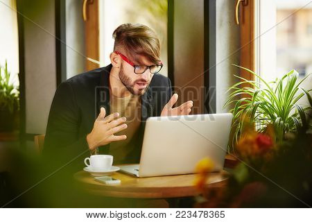 Expressive misunderstanding man sitting and working at laptop in cafe.