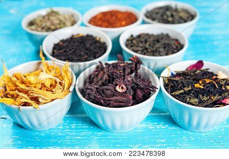 herbs and teas in bowls to make tea on blue table background closeup