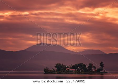 Small home on the tiny island in the middle of the stunning Lake Maninjao at sunset, Sumatra Island, Indonesia