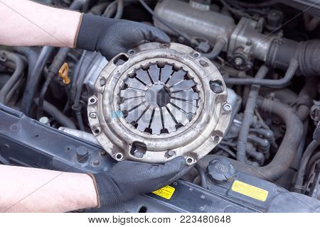 Car mechanic wearing protective work gloves holds old clutch basket over a car engine
