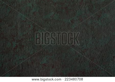 Abstract textured background of putty, painted in greenish-brown color. Imitation of surface of stone. Rough texture as wall pattern