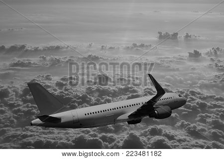 Passenger aircraft over clouds, plane, sky, clouds in grayscale