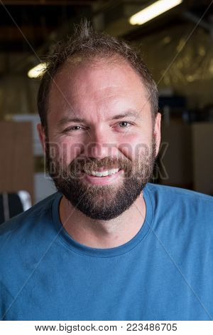 Headshot portrait of a man in a blue shirt with a dark beard on his face with simple studio lighting.