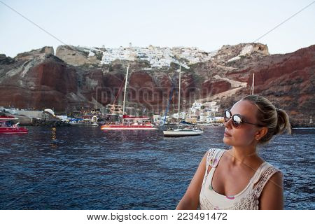 Woman traveling with the boat on distant island summer vacation,enjoying sun on her face.Holiday anticipation,open sea,cruise.Europe summer holidays.Exotic travel on remote place.Relaxing sunset scene