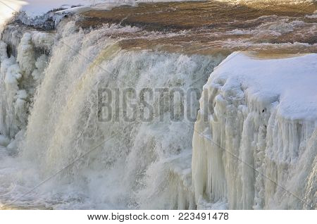Chaprin River waterfall flowing with winter snow and ice