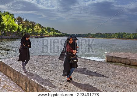 Isfahan, Iran - April 24, 2017: Three unknown women in a black religious veil stroll by the river Zayandeh.