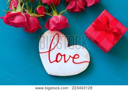Gift box and bouquet of roses and gingerbread in the shape of heart with the inscription love for holiday on wooden background. Mother's Day, Happy birthday , Women's Day. St. Valentines Day