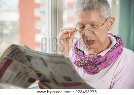 Senior elderly lady having troubles with her eye glasses, can't see well and can't read the small letters in the newspapers