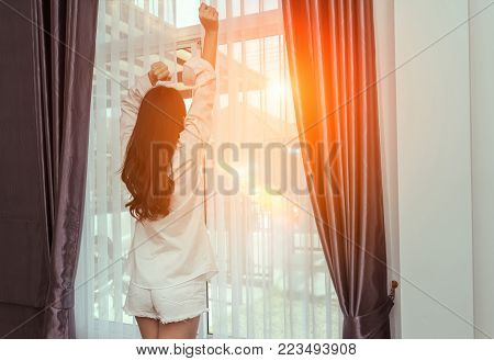 Woman wake up in the morning and open window after waking on bed relaxing good day in holiday with sunlight, rear view at living home lifestyle