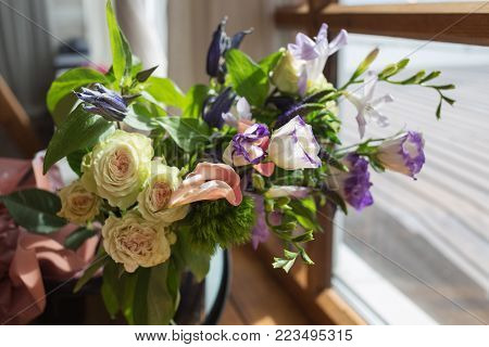 An amazing bouquet of diferent colourful flowers standing near the window. Romantic.