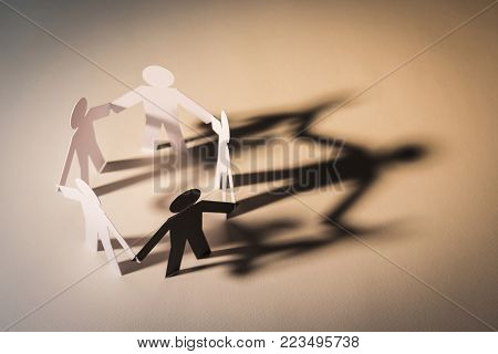 closed joining of five paper figure with black figure in hand down posture on light background. in concept of cooperation, weakness, fake and corruption.