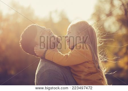 The father holds the daughter in his arms. A little girl pulls her father by the ears. Both are laughing. Happy childhood