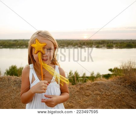 A little girl hides half of her face behind a toy on a stick. Toy star. In the background is a river.