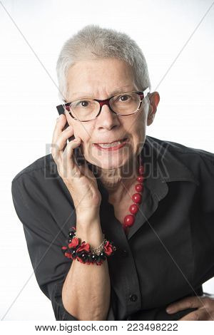 Furious and frustrated old woman yelling at her phone, displeased with customer service