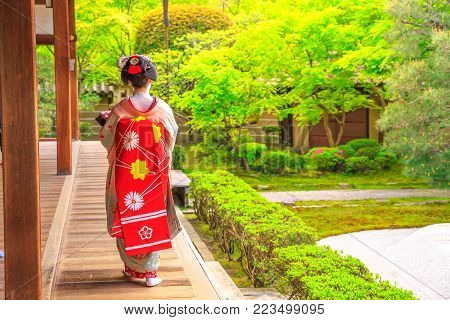 Kyoto, Japan - April 28, 2017: woman in geisha makeup walking outside corridors connecting buildings of Eikan-do Temple. Zenrin-ji is located in the eastern mountain of Kyoto's Higashiyama distric. Springtime.