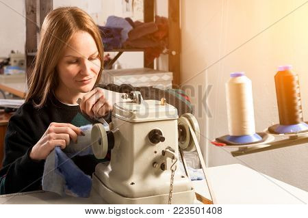 A young cheerful woman furrier smiles and sews a bright fur coat of natural blue fur on a sewing machine in the workshop