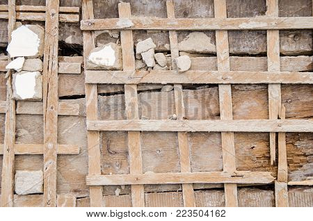 old grunge wall of planks with wooden lathing without stucco. vintage. poster