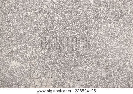 speckled cement covered with fine spray of light gray paint