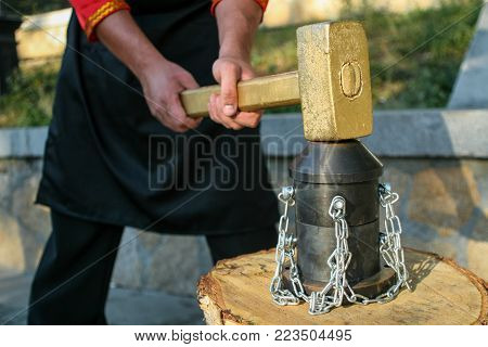 Blacksmith In A Red Shirt And Black Apron Knocking Hammer On The Anvil