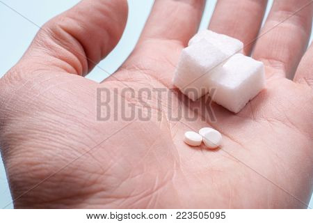 Choice of Sweetener in tablets or regular sugar. Alternative to sugar for diabetics. A man holds sugar and sugar substitute in his hand