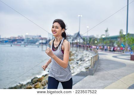 Sports concept. Beautiful girl is exercising on the beach with running. Beautiful girl is happy to exercise.  Beautiful girls like to exercise by running. People are exercising on the beach.