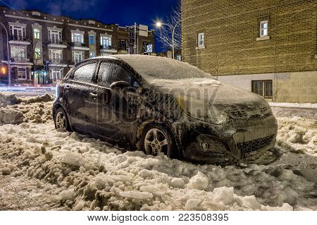 Montreal, Canada - 24 January 2017: Thick layer of ice covering car after freezing rain