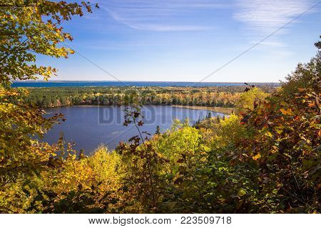 Scenic Autumn Lake Overlook. View from an overlook of a wilderness lake surrounded by lush autumn foliage in the Upper Peninsula town of Brimley, Michigan.