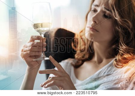 Miserable days. Upset thoughtful woman holding a wineglass while thinking out her problems