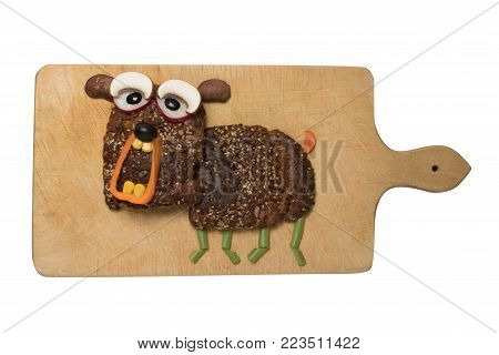 Dog compiled with bread and vegetables on cutting board