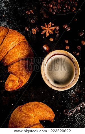 Homemade continental breakfast, coffee with spice, cane sugar, croissants. jam on a black rusty metal table, top view copy space
