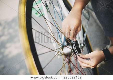 Close-up image of woman fixing bicycle chain