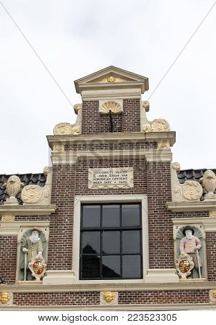 Top gable with memorial stone and sculptures of Huis van Achten in Alkmaar, Netherlands