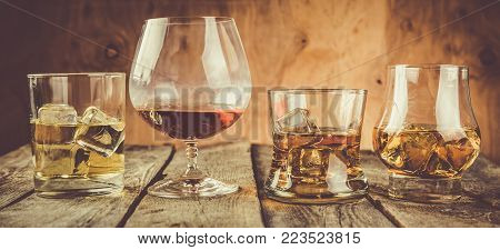 Different types of strong alcohol - bourbon, whiskey, scotch and cognac on rustic wood background