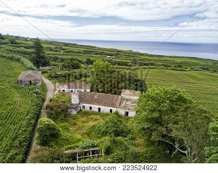 Aerial view of abandoned houses with fields and the Atlantic ocean in the background near the town of Ginetes on Sao Miguel Island, Portugal.