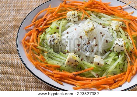 Vitamin salad from carrots, daikon and green radishes with cheese, vinaigrette sauce and flaxseed. Detox products. Prevention of avitaminosis, influenza and colds. Vegetarian, healthy and diet food