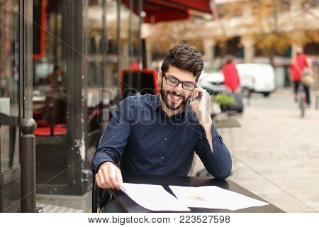 Skilled financial analyst chatting with tablet at cafe table and smiling. Resting young man using modern gadget. Concept of investment advisor at break and new technologies devices.