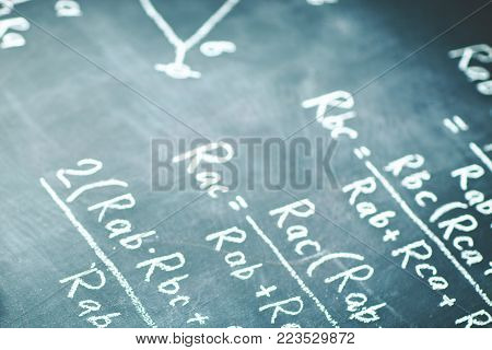 On the chalk Board written by the physical formula for the electric current. Scientific background.