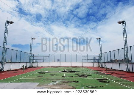 waste tennis court with ground breaking and waterlogging. the old condition deteriorated tennis court