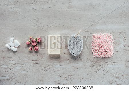 top view of stones, dried roses, natural soap, pumice and himalayan salt for spa on marble surface