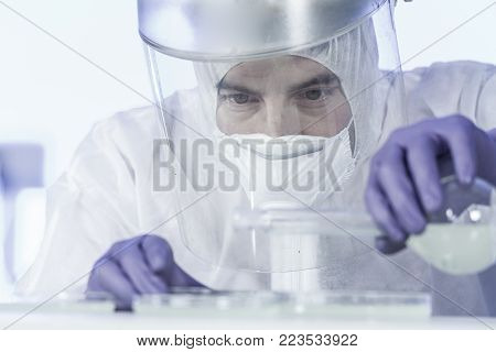 Life scientist researching in bio hazard laboratory. Focused life science professional working on experiment in high protection degree work laboratory. Healthcare and biotechnology.