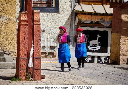 Shangri-La, China - September 25, 2017: Women walk in the Songzanlin Monastery, built in 1679, is the largest Tibetan Buddhist monastery in Yunnan province, known as Little Potala Palace.