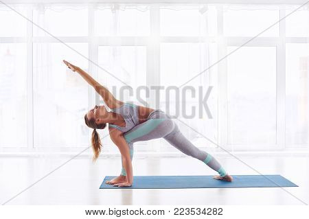 Beautiful young woman practices yoga asana Parivritta Parshvakonasana - Revolving side angle posture at the bright yoga class with large windows