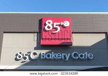 RICHARDSON, TX, USA-JAN 20, 2018:Close-up logo exterior of 85 C Bakery Cafe again blue sky. A Taiwanese chain of coffee shops and self-serve bakeries operated by Gourmet Master Co., Ltd